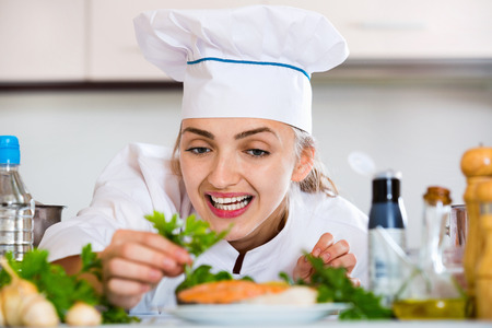 corcovado: Professional positive chef decorating dish with salmon for client Foto de archivo