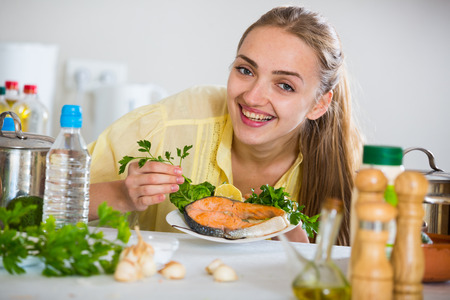corcovado: Young woman in yellow blouse with prepared trout at home Foto de archivo