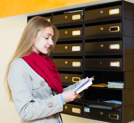 correspondencia: feliz mujer joven en la capa de comprobar la correspondencia en el lobby Foto de archivo
