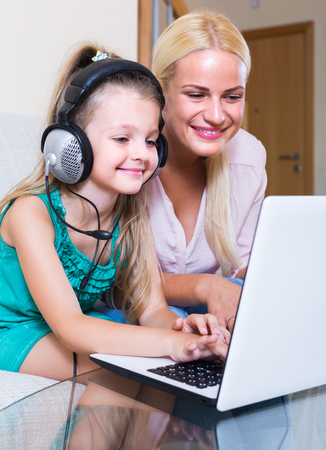 relatives: Smiling young blonde woman and her little daughter chatting with relatives online