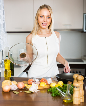 fryingpan: Blonde young housewife cooking from salmon at home kitchen