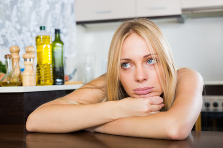heartbreak issues: Sad and lonely blonde woman sitting at kitchen Stock Photo