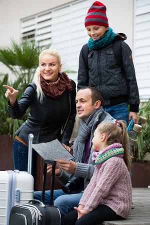 clase media: familia de clase media de cuatro miembros feliz dirección de verificación en un mapa aire libre Foto de archivo