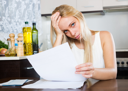 parsimony: Sad  blonde girl reading document at domestic kitchen Stock Photo