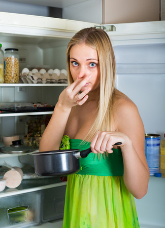 frowy: Young woman holding her nose because of bad smell from food near refrigerator at home