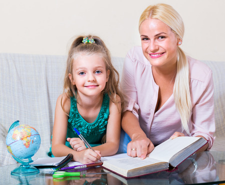 textbook: Private teacher and little girl studying with textbook at home Stock Photo