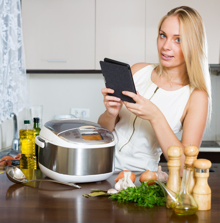 ereader: girl reading ereader and cooking with new crockpot at home interior