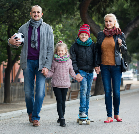 spouses: adult russian spouses with children posing in autumn park and smiling