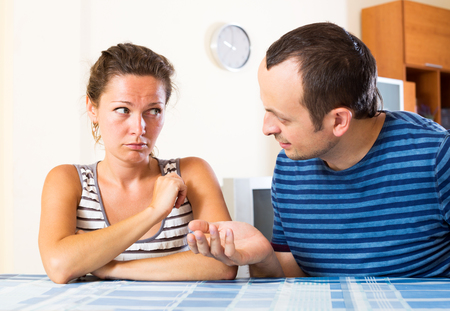 man scolding: Young depressed family sorting out their relationship. Focus on the woman