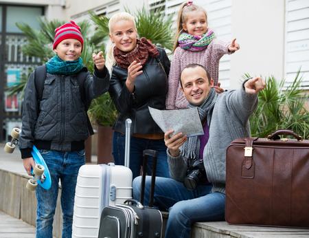 middle class: Feliz familia de clase media de cuatro miembros de comprobar una dirección en un mapa de la ciudad al aire libre