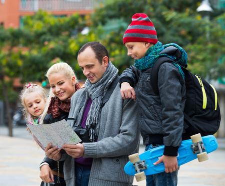 middle class: Feliz familia de clase media de cuatro personas el control de la dirección en un mapa de la ciudad