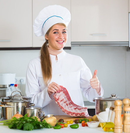 ribcage: Young woman cooking meat for dinner in home interior