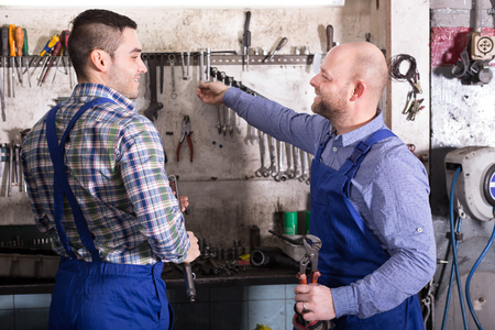 toiling: Two happy positive mechanics working at workshop