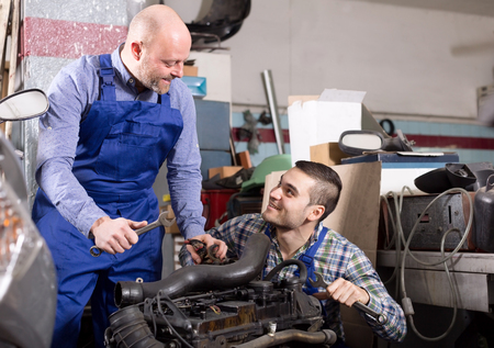 mounting holes: Happy mounting specialists working at auto repair shop.