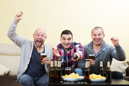 fandom: Three male friends sitting at table with beer and commenting footbal Stock Photo