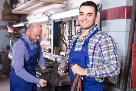 metalworker: Portrait of two happy men working with tools in a workshop