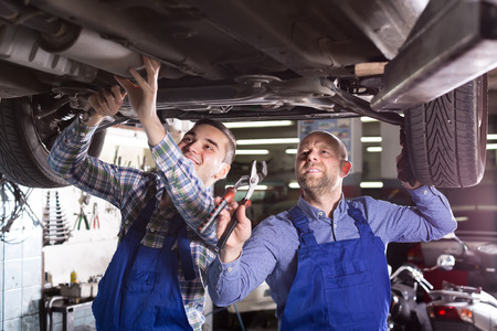 mounting holes: Two professional car mechanics checking up pressure in tires at workshop Stock Photo