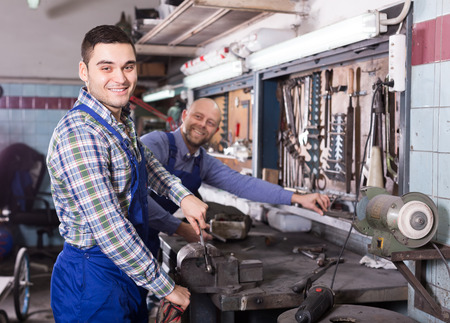 toiling: Two positive workmen toiling at the locksmiths workshop and smiling Stock Photo