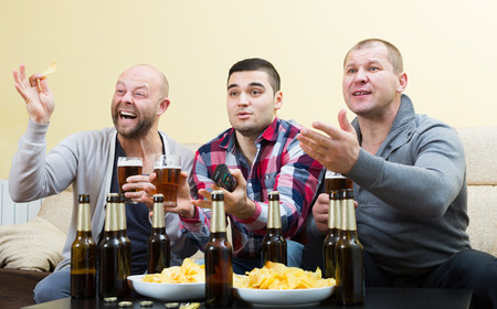 fandom: Three  european male friends sitting at table with beer and commenting sport tv channel