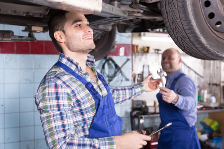 mounting holes: Two car mechanics checking up pressure in tires at workshop