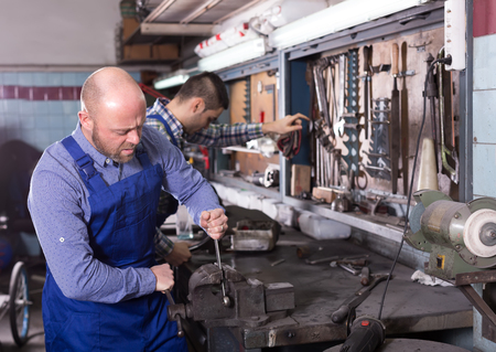 journeyman: Two mechanics wearing workwear using tools in a workshop