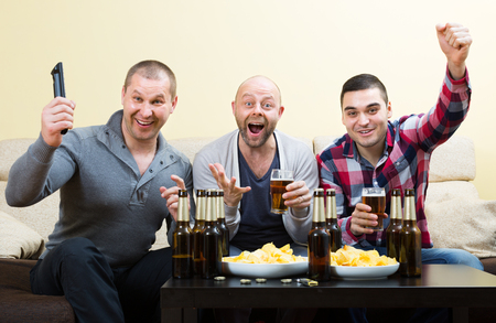 fandom: Three excited men drinking beer and watching football game indoor Stock Photo