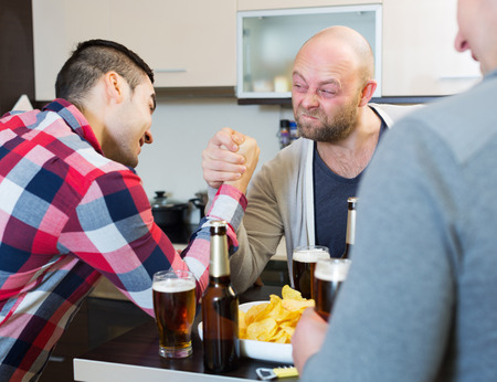 bout: Smiling and drunk men armwrestling, their friend supporting in kitchen at home Stock Photo