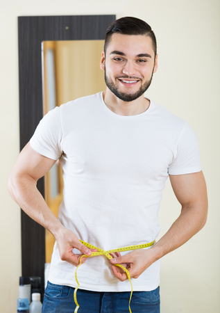russian man: Handsome russian man measuring his bicep and body Stock Photo