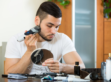 electric razor: Handsome man shaving face with electric razor