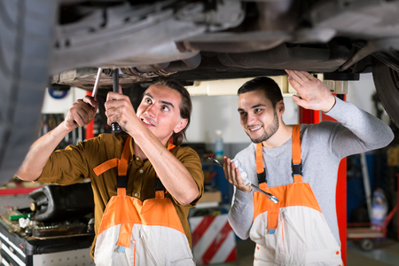 exhaust system: Positive mechanics in white and orange coveralls at automotive service station are repairing exhaust system of a lifted up car