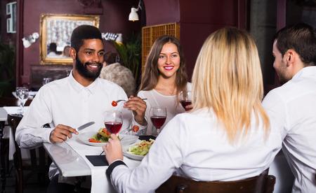 middle class: Gente de clase media felices disfrutando de la comida en la cafetería y hablando