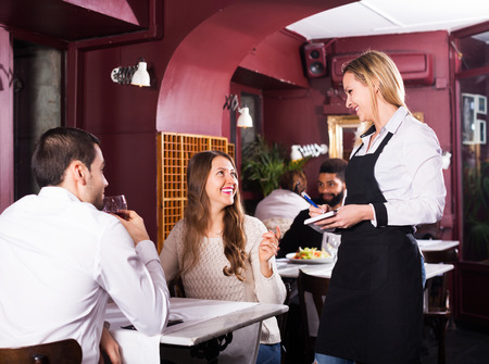 service desk: Smiling adult spouses having date in middle class restaurant. Focus on blonde girl Stock Photo