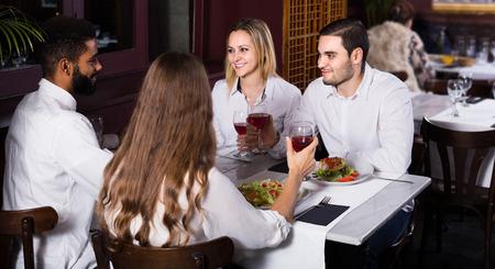 clase media: Clase media Popular Europeo felices disfrutando de la comida en la cafeter�a y hablando Foto de archivo