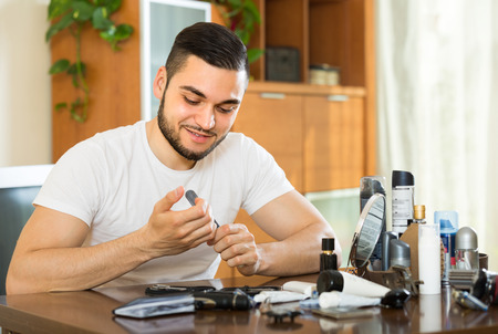 positiv: Smiling young handsome guy doing manicure at home Stock Photo
