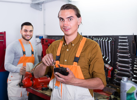 toiling: Two cheerful positive mechanics toiling in locksmiths workshop and smiling Stock Photo