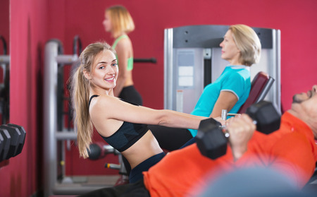 anaerobic: Active cheerful  smiling people  weightlifting training in modern health club