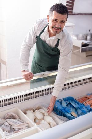 frozen fish: Mature salesman near display with frozen fish in supermarket Stock Photo