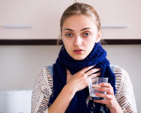 persona de pie: Chica con anginas de tomar la medicina y hacer g�rgaras la garganta en la cocina