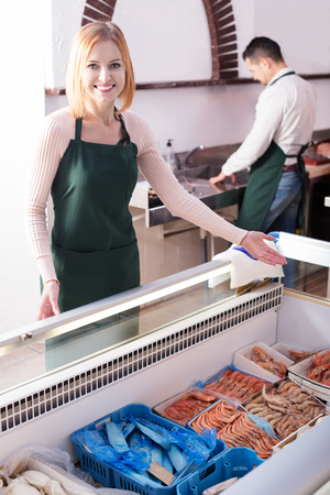 frozen fish: Two positive sellers standing near fridge with frozen fish