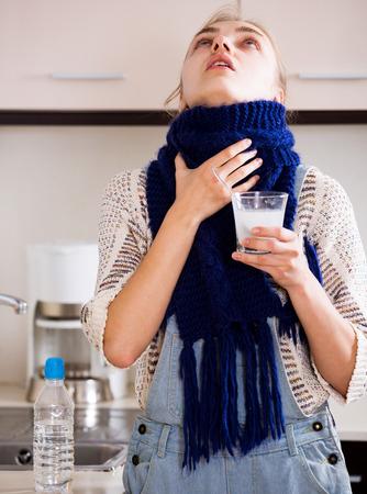 Portrait femme avec esquinancie prendre des médicaments et de se gargariser la gorge dans la cuisine