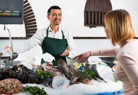 fish selling: Shop employee smiling selling fresh fish and chilled seafood to client