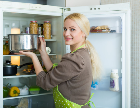 starving: Blonde woman looking for something in refrigerator in home