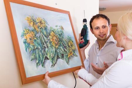 Man en vrouw opknoping kunst foto in frame op de muur samen. Focus op de mens Stockfoto