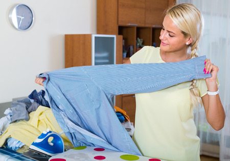 spanish woman: Portrait of cheerful spanish woman with iron and laundry Stock Photo