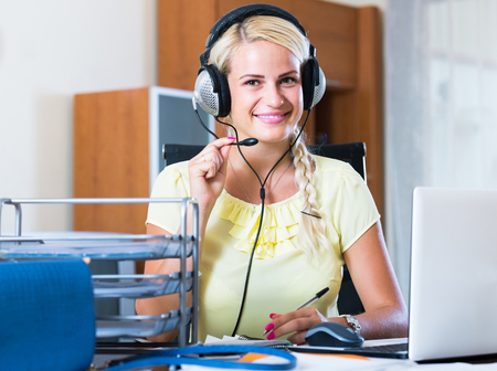 answering: smiling european girl answering the call of technical support and smiling
