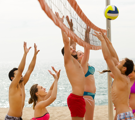 freetime: Heated smiling friends playing volleyball at sandy beach