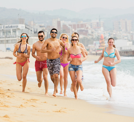 freetime: Happy friends running in swimwear at sea beach at sunny day