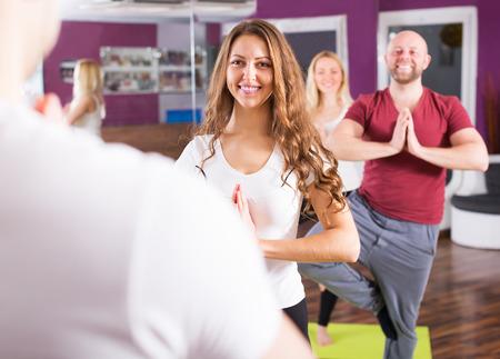 estudiantes adultos: Las personas felices que estudian en la escuela nueva posición de yoga Foto de archivo