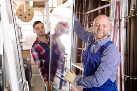 workmen: Smiling workmen with windows production at modern factory Stock Photo