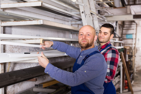 enginery: Couple of workmen 30 years old  inspecting window frames at factory